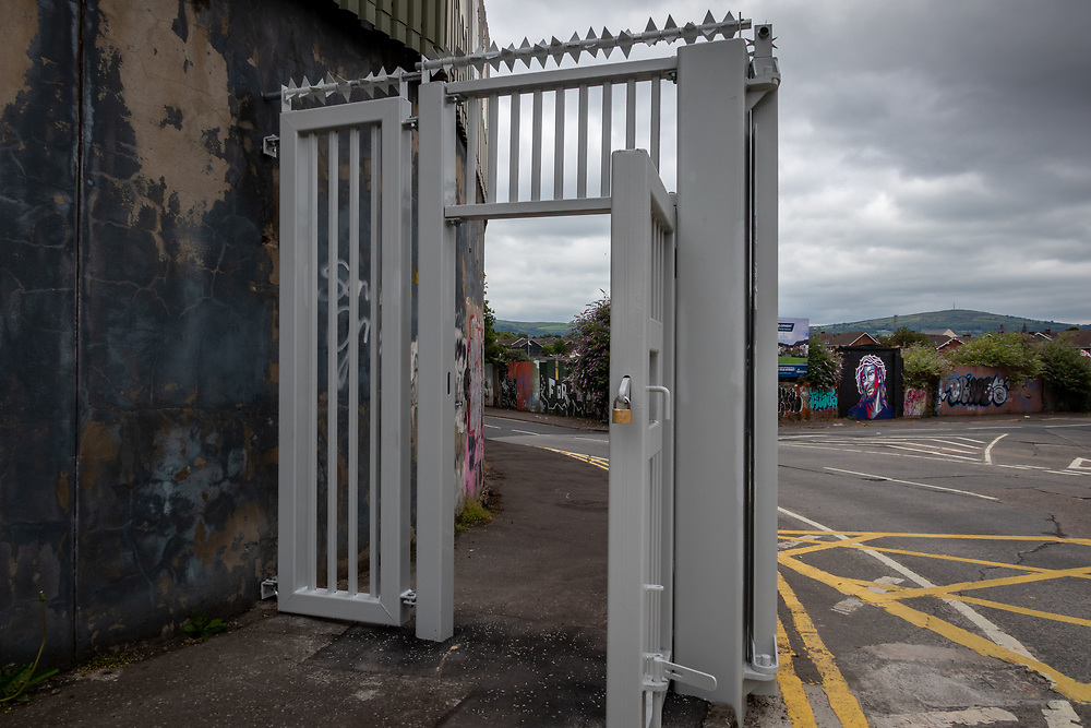 Standing on the nationalist side.The Belfast Peace Walls, separates catholic and protestant communities in Northern Islands Belfast. Security gates are closed every night and reopened at dawn in West Belfast.