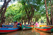 Tour guides wait to give tourists boat rides through the flooded forest south of Kampong Phluk, Cambodia.