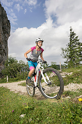 Mountain biker riding on uphill, Kampenwand, Bavaria, Germany