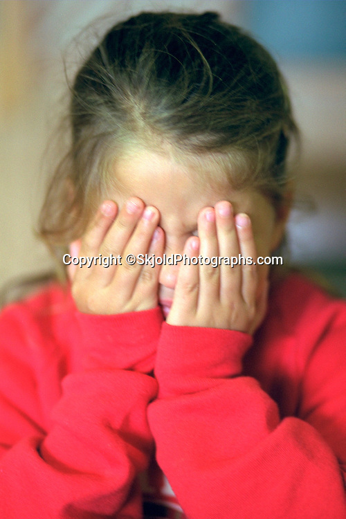 Girl age 6 covering eyes with hands at family cabin.   Michigan USA