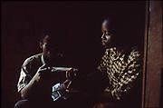 Emmanuel Singizumakiza, a health educator shows a boy how to use a condom. Kibileze, Rwanda.
