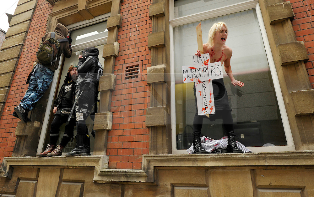 NOTE TO EDITORS - CONTAINS NUDITY © Licensed to London News Pictures. 02/04/2012.  Performance artist and human rights activist Milly Fish (right) takes part in a protest against unmanned aerial vehicles or drones used for military operations in Afghanistan and elsewhere and for surveillance in the UK.  The protest was outside a conference on UAVs at Armada House in Telephone Avenue in central Bristol.  Police made several arrests...Photo credit : Simon Chapman/LNP