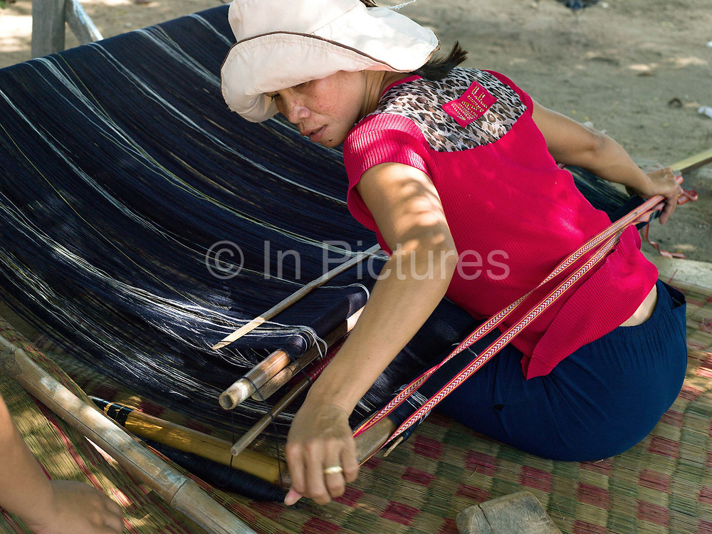 A Hindu Cham woman weaves cotton and silk fabric on a back-strap loom outside her home in My Nghiep village, Ninh Thuan province, Central Vietnam.  The resulting fabric is used to make the traditional sarong style skirt worn by Cham women on special occasions or sold to local customers in the village. The Cham people are remnants of the Kingdom of Champa (7th to 18th centuries) and are recognised by the government as one of Vietnam's 54 ethnic groups.