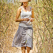 Looking very summery, Peace Corps volunteer Rachael Honick strolls through the tall grass between the fields of her village, Koumbadiouma in Kolda, Senegal.