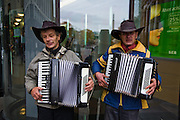 Men play accordions on a street for donations in Riga, the capital of Latvia.