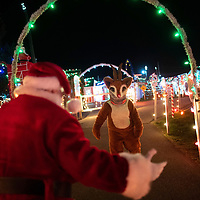 BERNVILLE, PA:  Milt Stoltzfus, 59, in his 12th year as Santa, greets  Rudolph the Red nosed Reindeer wearing a scarf face mask due to the coronavirus (COVID-19) pandemic at Koziar's Christmas Village in Bernville, PA on December 7, 2020. Once a working dairy farm, this family run attraction, in its 73rd year, features over a million holiday lights.  The pandemic has forced difficult decisions about maintaining the holiday tradition of visits to Santa Claus versus safety concerns.  Plexiglass dividers, face shields, and physical distancing are among the precautions for those locations that have proceeded with Santa photo opportunities.  CREDIT:  Mark Makela for The New York Times