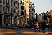 A man crosses an eerily quiet Regent Street in front of vacant taxis in the early evening at Oxford Circus in London on March 27th, 2020. The centre of London is extremely quiet with almost every business closed and very few people about because of the Governments lockdown measures due to the Coronavirus crisis.