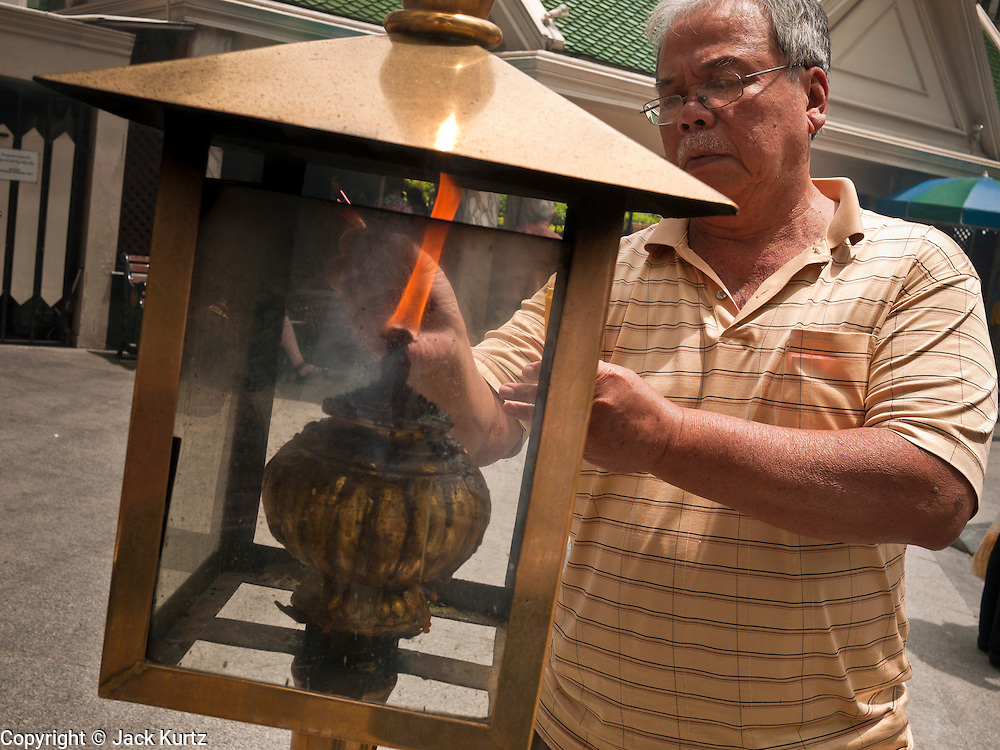 11 JULY 2011 - BANGKOK, THAILAND:   A man lights incense before praying at the Erawan Shrine in Bangkok. The Erawan Shrine (in Thai San Phra Phrom) is a Hindu shrine in Bangkok, Thailand that houses a statue of Phra Phrom, the Thai representation of the Hindu creation god Brahma. A popular tourist attraction, it often features performances by resident Thai dance troupes, who are hired by worshippers in return for seeing their prayers at the shrine answered. On 21 March 2006, a man vandalised the shrine and was subsequently killed by bystanders. The shrine is located by the Grand Hyatt Erawan Hotel, at the Ratchaprasong intersection of Ratchadamri Road in Pathum Wan district, Bangkok, Thailand. It is near the Bangkok Skytrain's Chitlom Station, which has an elevated walkway overlooking the shrine. The area has many shopping malls nearby, including Gaysorn, CentralWorld and Amarin Plaza. The Erawan Shrine was built in 1956 as part of the government-owned Erawan Hotel to eliminate the bad karma believed caused by laying the foundations on the wrong date..The hotel's construction was delayed by a series of mishaps, including cost overruns, injuries to laborers, and the loss of a shipload of Italian marble intended for the building. Furthermore, the Ratchaprasong Intersection had once been used to put criminals on public display. An astrologer advised building the shrine to counter the negative influences. The Brahma statue was designed and built by the Department of Fine Arts and enshrined on 9 November 1956. The hotel's construction thereafter proceeded without further incident. In 1987, the hotel was demolished and the site used for the Grand Hyatt Erawan Hotel.     PHOTO BY JACK KURTZ
