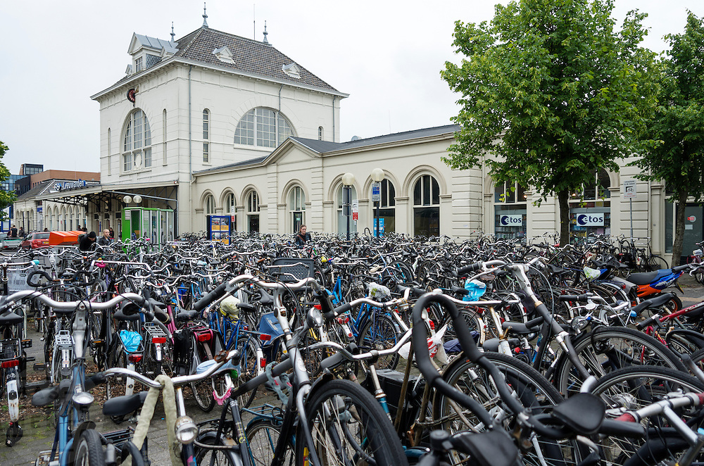 Voor het station in Leeuwarden staat de fietsenstalling vol met fietsen.<br /> <br /> At the train station of Leeuwarden, the bike parking is full with bicycles.