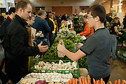 A young vendor at Toronto's St. Lawrence farmers' market bags a customer's purchase.