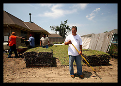 May 5th, 2006. New Orleans, Louisiana. Saint Bernard Parish, east of the city. Major James Pohlmann of the St Bernard Sheriff's dept stands outside his gutted home as Latino immigrants celebrate Cinqo de Mayo installing new turf. Major Pohlmann witnessed the destruction of hurricane Katrina first hand and was amongst the first responders to begin rescuing people from their flooded, devastated homes and businesses.