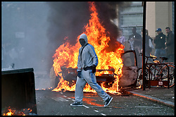 A Rioter in Hackney by a burning car on the streets of London, during the London riots and disturbances, August  2011. Photo By i-Images