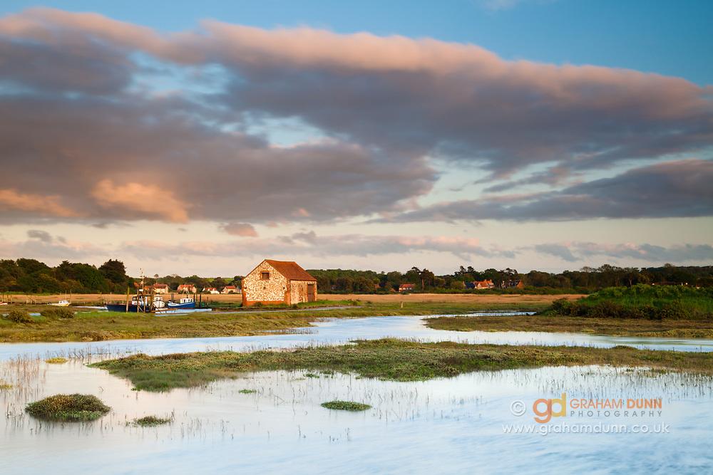 A high tide isolates Thornham Harbour's Coal Barn on the North Norfolk coast. East Anglia.