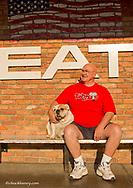Proprieter of the Bulldog Saloon, Buck May and his Bulldog, Mauade in downtown Whitefish, Montana, USA