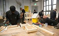 DEU, Deutschland, Germany, Berlin, 17.12.2015: Flüchtlinge arbeiten in einer Werkstatt der Flüchtlings-Initiative der Handwerkskammer, arrivo Berlin, in der Innung für Metall- und Kunststofftechnik. El Alhagie Gailou aus Ghana (links) beim Arbeiten an einem Tisch und Hessan Adam aus Ghana (rechts) beim Streichen eines Holzhauses.