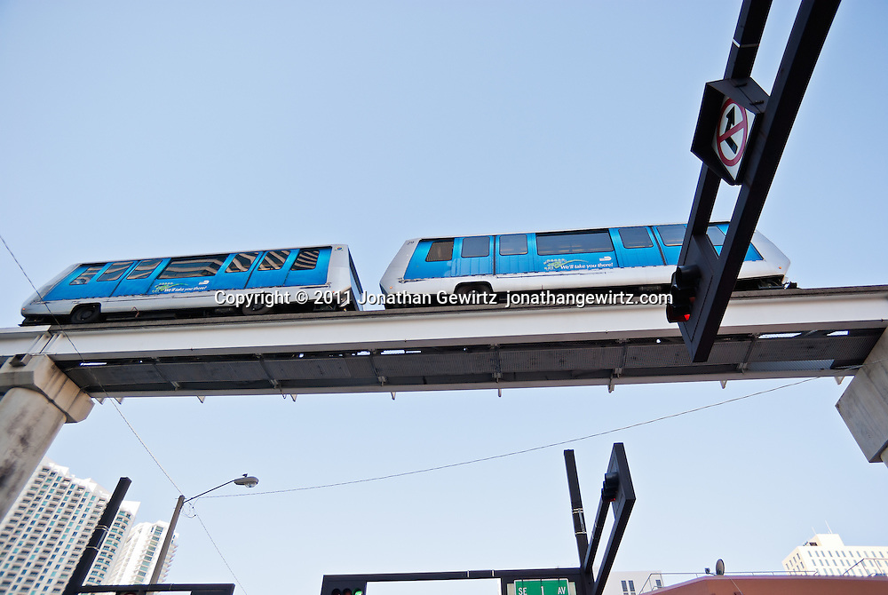 Two cars of the Miami Metromover automated urban transit system travel overhead along an elevated track paralleling SE 1st Avenue. WATERMARKS WILL NOT APPEAR ON PRINTS OR LICENSED IMAGES.