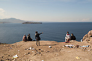 Migrants and refugees sit on a clifftop overlooking Turkey (out of shot on the right), on the Greek island of Lesvos.