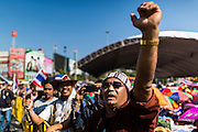 """14 JANUARY 2014 - BANGKOK, THAILAND: Thai anti-government protestors cheer while a speaker condemns caretaker Prime Minister Yingluck Shinawatra at Victory Monument. Tens of thousands of Thai anti-government protestors continued to block the streets of Bangkok Tuesday to shut down the Thai capitol. The protest, """"Shutdown Bangkok,"""" is expected to last at least a week. Shutdown Bangkok is organized by People's Democratic Reform Committee (PRDC). It's a continuation of protests that started in early November. There have been shootings almost every night at different protests sites around Bangkok, but so far Shutdown Bangkok has been peaceful. The malls in Bangkok are still open but many other businesses are closed and mass transit is swamped with both protestors and people who had to use mass transit because the roads were blocked.     PHOTO BY JACK KURTZ"""