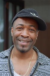 Portrait of man wearing baseball cap standing outside smiling,