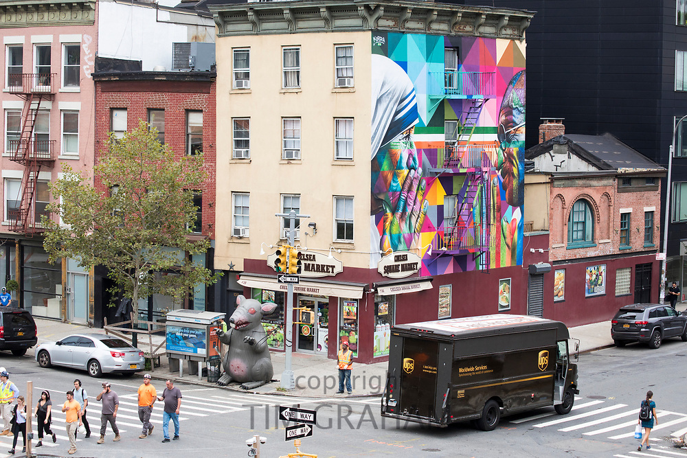 Street corner scene with UPS courier delivery truck, traffic lights, mural and Chelsea Square Market store at West 18th Street and Tenth Avenue in New York City, USA