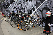 Locked up bikes and a construction hoarding featuring dozens of London faces in the City.