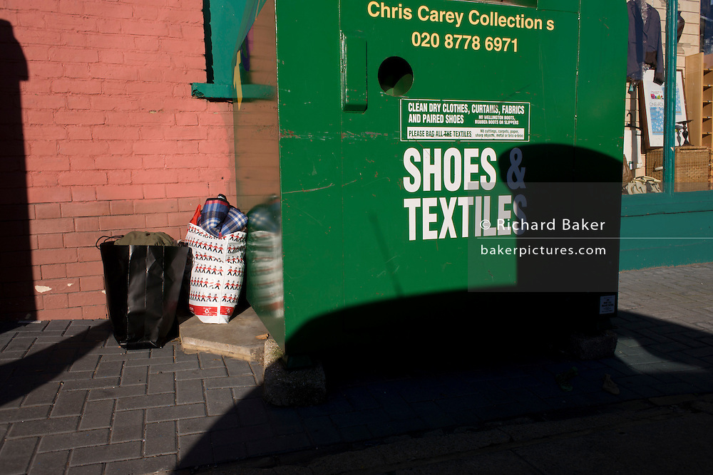 Bags of second-hand clothing left near a charity shop receptacle in a London street.