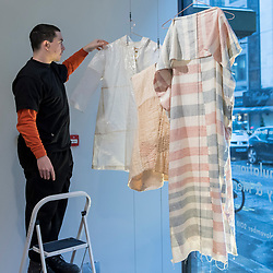"© Licensed to London News Pictures. 20/11/2018. LONDON, UK. A staff member hangs textiles by Hala Kaisow. Preview of ""Accumulation:  Legacy and Memory"", an exhibition presented by Art Bahrain Across Borders during Bahrain Art Week.  Works from 11 emerging and established Bahraini artists is on display 20th to 26 November at Alon Zakaim Fine Art gallery in Mayfair.  Photo credit: Stephen Chung/LNP"