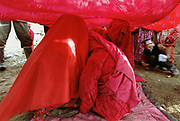 """The bride, along with her sisters and other close female relatives are squatting under a red cloth in front of the ceremonial yurt while the men around the cloth are throwing candies on the cloth and distributing """"bortsok"""" (fried dough), to bring good luck to the wedding. Meanwhile, the girls are weeping and crying, signifying the upcoming """"loss"""" of the bride to her husdand's family.<br /> The Kyrgyz wedding ceremony of Koormoochoo Saïra (son of Yunus Amid) in Utch Djelgha summer camp, 5th August 20005.<br /> <br /> Adventure through the Afghan Pamir mountains, among the Afghan Kyrgyz and into Pakistan's Karakoram mountains. July/August 2005. Afghanistan / Pakistan."""