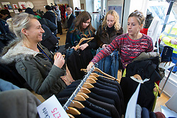 © licensed to London News Pictures. London, UK 22/11/2013. People browsing clothes and shoes donated by David and Victoria Beckham to help raise money for Philippine typhoon disaster at the British Red Cross branch in Chelsea, London. Photo credit: Tolga Akmen/LNP