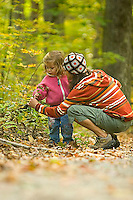Young woman and child exploring in forest in rural New Hampshire. Lake Ossipee, NH
