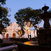 Strings of lights are wrapped around the trees in the central town square in Antigua Guatemala. Famous for its well-preserved Spanish baroque architecture as well as a number of ruins from earthquakes, Antigua Guatemala is a UNESCO World Heritage Site and former capital of Guatemala.