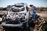 Melissa Vaughn retrieves items from her destroyed car outside of Briarwood elementary school where her child is a student in Oklahoma City, Oklahoma May 22, 2013.  Rescue workers with sniffer dogs picked through the ruins on Wednesday to ensure no survivors remained buried after a deadly tornado left thousands homeless and trying to salvage what was left of their belongings. Curvature of horizon in the photo is due to an ultra-wide angle lens.  REUTERS/Rick Wilking (UNITED STATES)