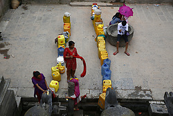 June 9, 2017 - Lalitpur, Nepal - Nepalese women queue with their jerry cans to fill water from an ancient water spout inside UNESCO World Heritage Site premise at Patan Durbar Square in Lalitpur, Nepal on June 9, 2017. (Credit Image: © Skanda Gautam via ZUMA Wire)