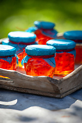 Jars of Bramley apple and chilli jelly on a tray