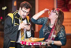 © Licensed to London News Pictures . 30/10/2016 . Manchester , UK . A man and a woman share cheesy chips and a pizza . Revellers on a night out , many in fancy dress , on the weekend before Halloween . Photo credit : Joel Goodman/LNP