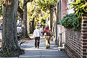 An elderly couple walk down historic Meeting Street in Charleston, South Carolina.