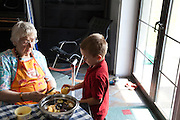 Polish great grandmother cutting ripe yellow apples with great grandson age 86 and 6. Zawady Central Poland