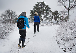 © Licensed to London News Pictures. 27/12/2017. Dorking, UK. Hill walkers Lydia Farzin-Nia (R) and Charlotte Turner reach the top of Leith Hill after early morning snow showers and low temperatures. Photo credit: Peter Macdiarmid/LNP