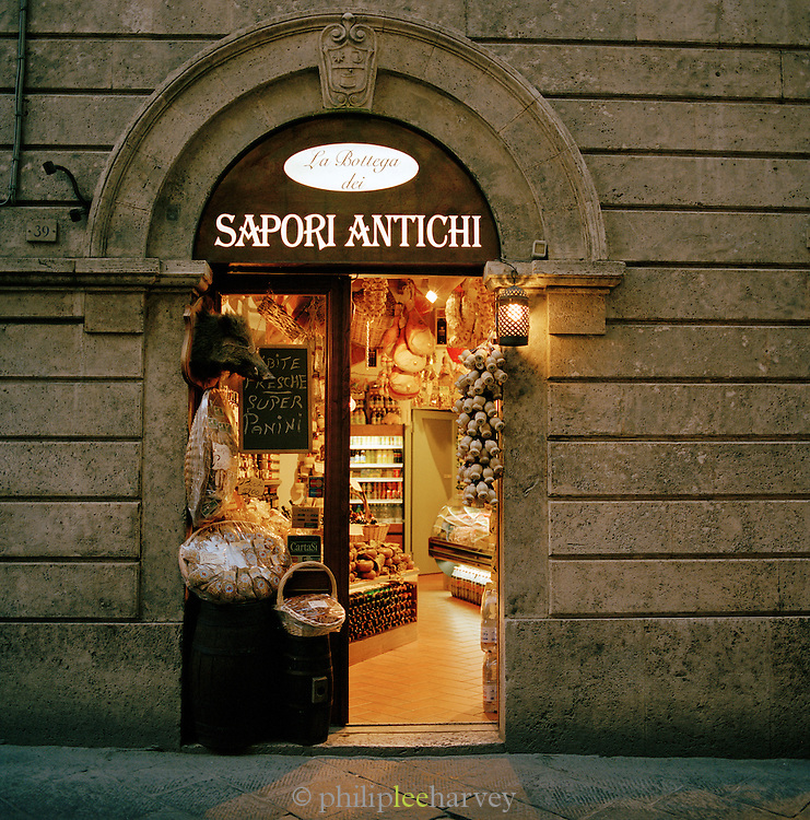 Grocery store doorway display at night, Siena, Tuscany, Italy