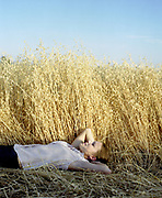 Young woman lying in oat field gazing at the sky