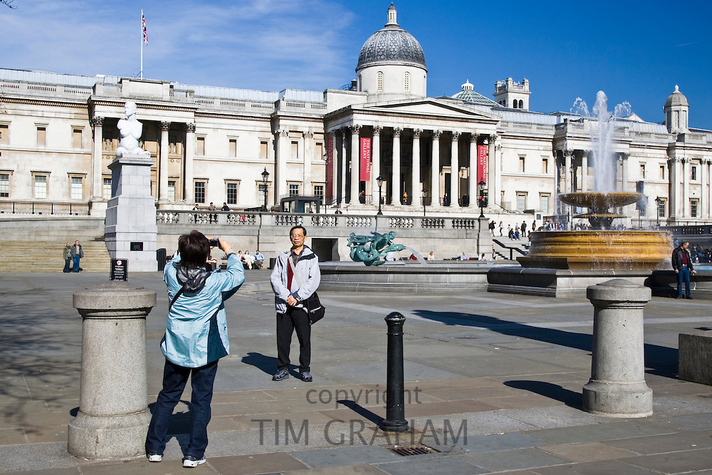 Tourists pose for photographs in front of National Gallery in Trafalgar Square, London, United Kingdom