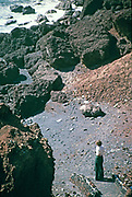 Woman standing on beach with volcanic rocks and lava flows, Lanzarote, Canary Islands, Spain in 1979