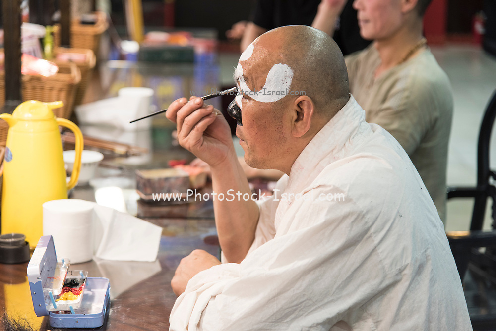 Traditional Chinese actor applies makeup before a performance in a Chinese theatre. Photographed in Chengdu, Sichuan, China