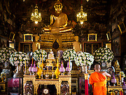 """11 SEPTEMBER 2017 - BANGKOK, THAILAND: A monk in the viharn (prayer hall) at Wat Arun. Renovations are nearly finished at Wat Arun on the Thonburi side of the Chao Phraya River in Bangkok. Wat Arun is famous for its Khmer style main """"prang"""" (chedi). It was originally built in the Ayutthaya Period and rebuilt to its current form in the time of Rama II.      PHOTO BY JACK KURTZ"""