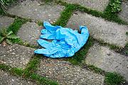 Nederland, Nijmegen, 27-3-2020 Een blauwe latex handschoen ligt op straat. Iemand heeft hem aangehad, iets vastgepakt en weer weggegooid ivm het coronavirus. Dit type handschoen wordt normaalgesproken in de medische sector gebruikt en worden door professionals in een afvalbak gedaan nagebruik .Foto: Flip Franssen