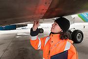 Nesrine, an aircraft inspector checks loose plates of a plane. At Roissy, Nesrine, 34, works as a technical inspector  for the DGCA (Directorate General of Civil Aviation) - she is the only female technical controller at the airport of Roissy-en-France. She can stop a Boeing taking off and make the 300 passengers leave the airplane. Nesrine Chkioua is the only woman controller at Roissy Airport and one of three women doing this job in France.<br /> <br /> <br /> À Roissy, Nesrine, 34 ans, exerce le métier de contrôleur technique (CTE) pour la DGAC (Direction générale de l'aviation civile) - elle est la seule femme contrôleur technique à l'aéroport de Roissy-en-France.  Elle peut immobiliser un Boeing, retarder le décollage et même faire débarquer les 300 passagers d'un long-courrier. Nesrine Chkioua est la seule contrôleur femme à Roissy aéroport et est une des trois femmes à exercer ce métier en France.