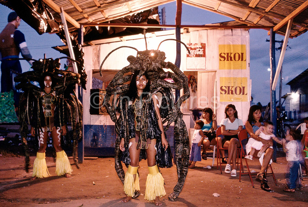 """Brazil -Parintins - The Boi Bumba carnival and a a woman and her giant scorpion costum sit ina oudoor bar resting before entering the stadium, known as the Bumbodromo""""  to celebrate the three day event deep in the Amazon. The carnival serves to celebrate and re-enact Indian traditions and perpetuate myths and legends. It has evolved over time and involves the battle between to opposing bulls, known as Garantido and Caprichoso"""