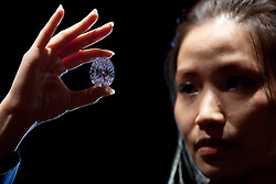© Licensed to London News Pictures. 09/09/2013. London, UK. A Sotheby's employee holds a 118.28 carat flawless oval diamond, which is estimated to achieve GB£35 million (US$28 million), at a press view held at the London based auction house's New Bond Street premises today (09/09/2013). The diamond, forming part of a sale of jewels and jadeite, is set to go on sale in Sotheby's Hong Kong on the 7th of October 2013. Photo credit: Matt Cetti-Roberts/LNP