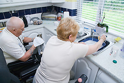Disabled couple doing the washing up together in their nonadapted kitchen,