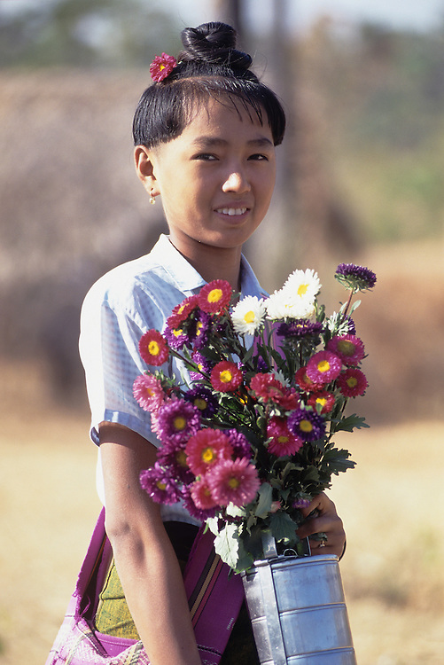 Young female student in uniform with flowers, Magwe Division, Central Myanmar